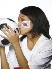 Frau mit koreanischen Flagge im Gesicht küsst Fußball