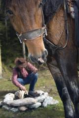 Junger Mann am Lagerfeuer , Pferde im Vordergrund , close-up