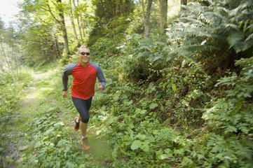 Junger Mann beim Joggen in Wald, Österreich, Salzburger Land