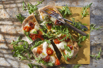 Pizza with tomato and arugula