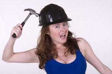 Young woman holding a hammer and wearing a hard hat