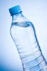 Close-up plastic bottle of drinking water obliquely on a blue ba