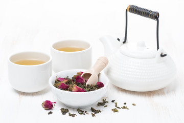 green tea with rosebuds, cups and teapot on white wooden table