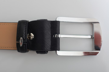 silver buckle of male black  leather belt on a white background