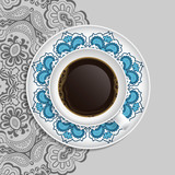 Cup of coffee and decorative ornament on a saucer and background
