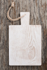 light wooden cutting board on a dark background, top view