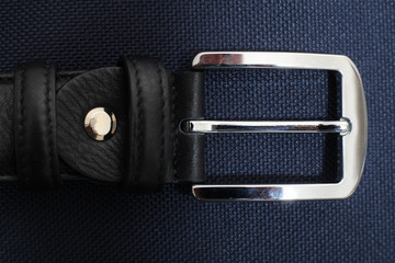 silver buckle of male black  leather belt on a black background