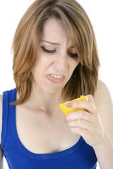 Frau verzieht Gesicht nach Biss in Zitrone