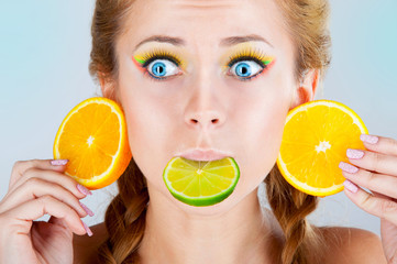 woman holds the lime in the mouth and oranges as earrings