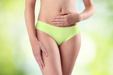 Woman's hands on stomach on green background