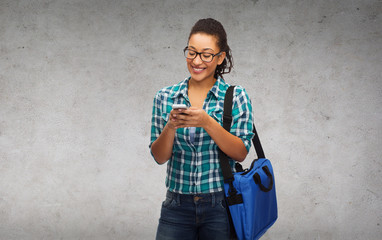 student in eyeglasses with smartphone and bag