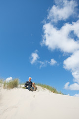 Man sitting with dog in the dunes
