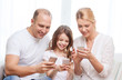 parents and little girl with smartphones at home