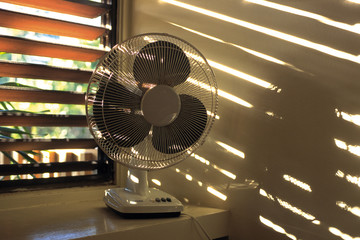Electric fan beside window