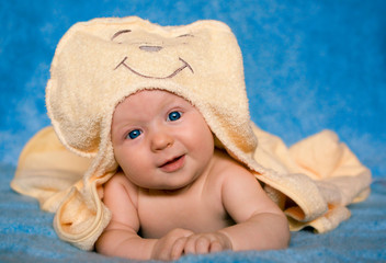 Smiling baby lying on a blue background
