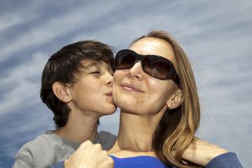Niño besando a madre rubia con gafas de sol