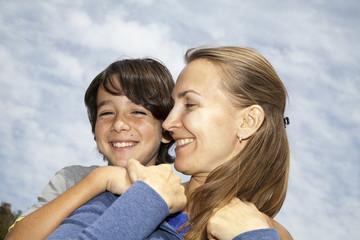 Niño abrazando a su madre mientras ambos sonríen