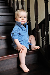 Portrait of a baby boy in a shirt at home