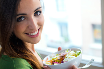 Woman eating salad. Portrait of beautiful smiling and happy Cauc