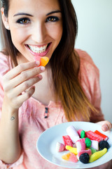 Cute young woman eating jelly candies with a fresh smile