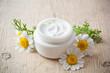 Leinwandbild Motiv container with cream and chamomiles
