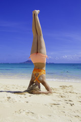 blond girl in bikini doing yoga at the beach
