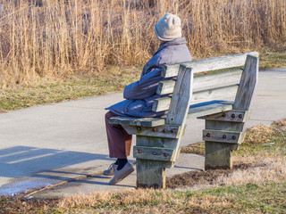 Lonely Person Sitting on Park Bench