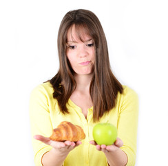 Doubtful woman holding an apple and croissant trying to decide w
