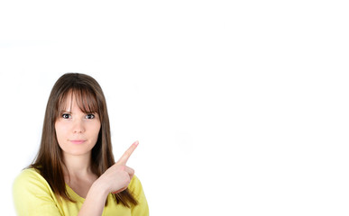 Young happy woman points hand at empty space with positive facia