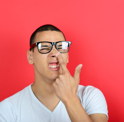 Portrait of a funny guy with finger in his nose against red back