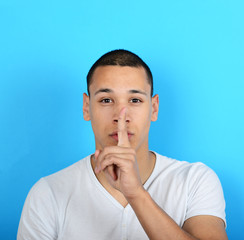 Portrait of man with gesture for silence against blue background