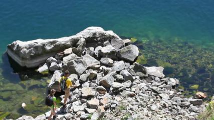 Two backpackers walk on rocky coast