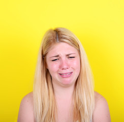 Portrait of sad girl against yellow background