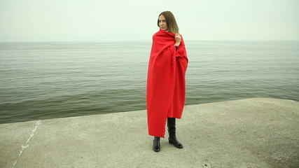 Lonely sad girl in red blanket on the sea shore
