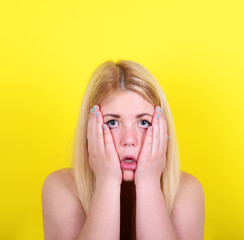 Portrait of surprised girl against yellow background