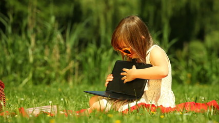 Little girl child in sunglasses using tablet outdoor