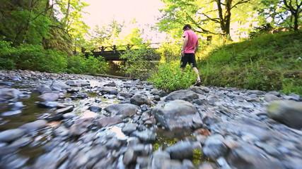 Glide Cam Male Walking Over Rocks