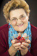 Senior woman holding cherries