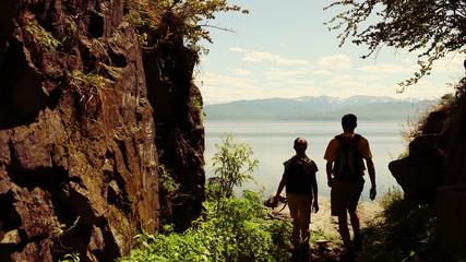 Two backpackers walk on rocky coast of big lake