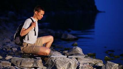 Backpacker walks on rocky coast