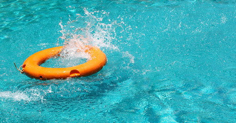 Orange life buoy splash water in the blue swimming pool