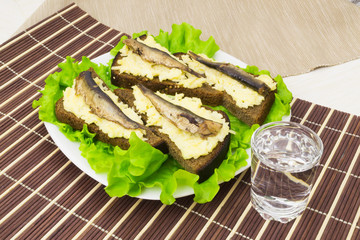 Sprats on bread with garlic cheese and a glass of vodka
