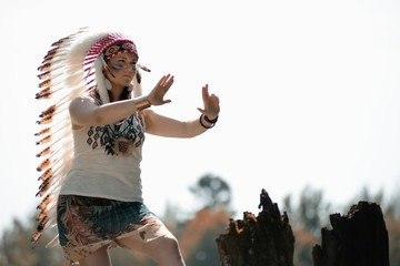 Girl in war bonnet headdress does shaman movements