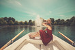 canvas print picture - Woman relaxing in a rowing boat on lake