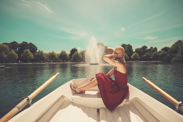 Woman relaxing in a rowing boat on lake