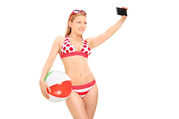 Woman holding a beach ball and taking selfie