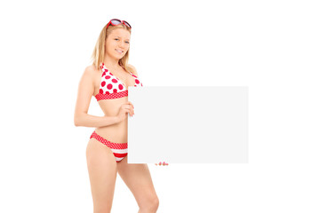 Attractive woman in bikini holding a blank banner