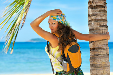 Happy young woman standing with backpack on coast sea and lookin