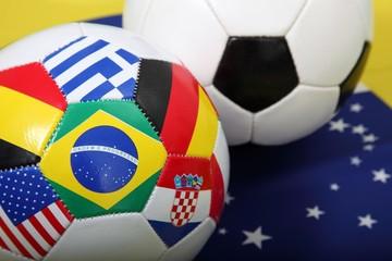 Fussbälle mit Flaggen-Symbolen auf Flagge von Brasilien