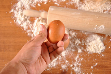 hand picking eggs and flour